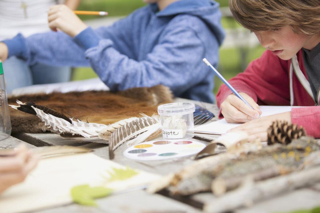 Schüler*innen beim Biologieunterricht draußen