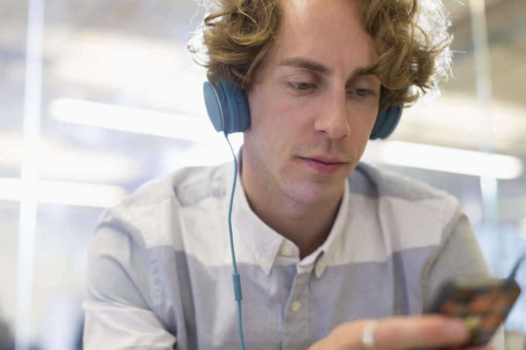 Mann mit Kopfhörern, der Podcast hört