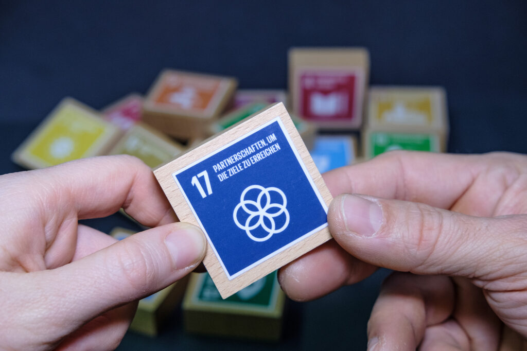 SDG Würfel Ziel 17 mit zwei Händen